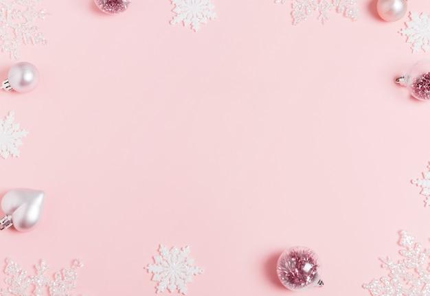Праздничный творческий синий серебряный рождественский праздник композиция, рождественский декор праздничный шар с лентой, снежинки на розовом фоне. рождество, зима, новогодняя концепция. плоская планировка, вид сверху, копия пространства