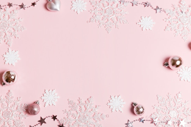 Праздничный творческий белый серебряный рождественский праздник композиция, рождественский декор праздничный шар с лентой, снежинки на розовом фоне. рождество, зима, новогодняя концепция. плоская планировка, вид сверху, копия пространства
