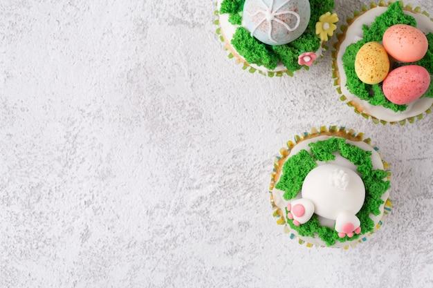 面白いバニー、卵、白い背景の上の草でお祝いカップケーキ。イースター休暇の概念。コピースペースのトップビュー
