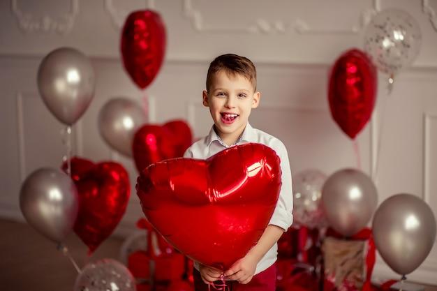 생일이나 발렌타인 데이를위한 축제 장식. 바람이 잘 통하는 회색 금속 풍선과 색종이. 그의 손에 빨간 하트 모양의 풍선을 들고 명랑 아이 소년