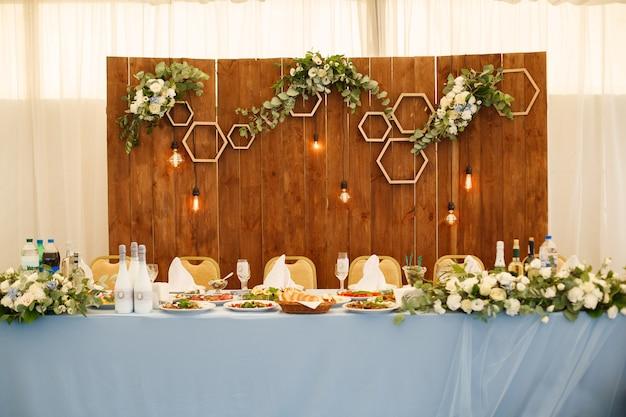 お祝いの装飾が施されたレストランホール。お祝いの結婚式や誕生日パーティーの場所。プレート、グラス、レストランの料理とお祝いテーブル。