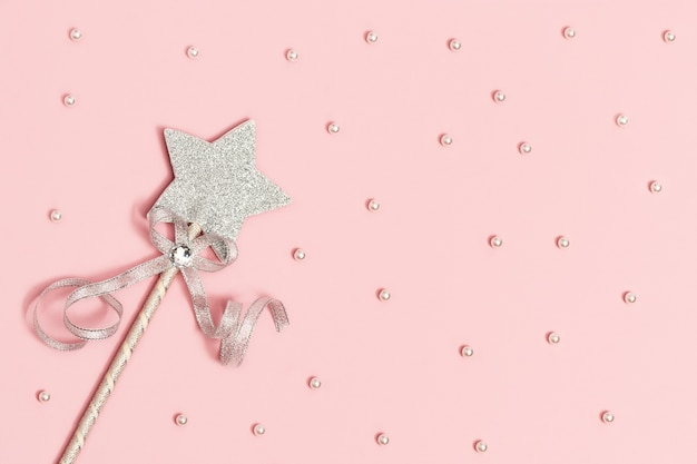 Festive decoration, bright silver star with sequins on soft pink background with white beads.