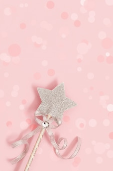 Festive decoration, magic wand, bright silver star with shine on soft pink background with bokeh.