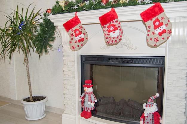 暖炉、靴下、ノームを備えたリビングルームのインテリアのお祝いの装飾が掛けられています。