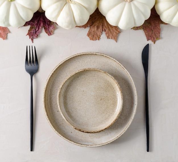 テーブルのお祝いの装飾。テーブルの上の空のプレート、電化製品、白いカボチャ。