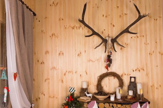 나무 벽에 장착된 사슴 뿔 아래 선반에 전통적인 장식품, 양초, 샴페인 플루트 2개가 있는 소박한 샬레에서 크리스마스를 위한 축제 장식 장식