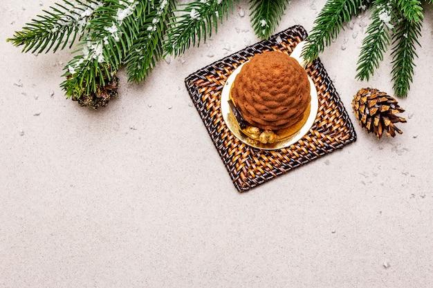 クリスマスのモミの実の形をしたお祝いデザート。新年の甘い御concept走のコンセプト。石のコンクリートの背景