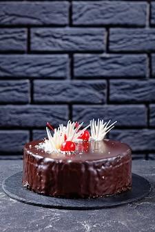 ホワイトチョコレートと缶詰のチェリーで飾られたダークチョコレートの釉薬で満たされたチェリーパイのお祝いの悪魔のチョコレートとチェリーのケーキ