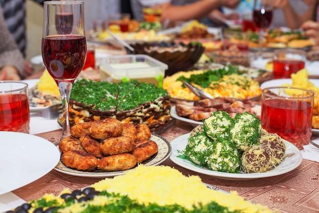 自宅でのお祝いディナー、クリスマスの日。ベーコン、チーズボール、衣で揚げた魚、カツレツ、マッシュポテト、レバーケーキ、グラスに入ったフルーツコンポートなど。