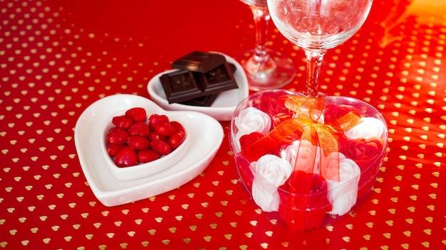 お祝いのディナー。日にち。バレンタインデーの赤い背景。ディナーのコンセプトが大好き