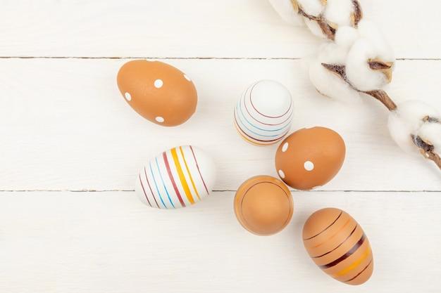 お祝いのイースターの背景。綿の花の枝と木製の背景に塗られた卵。