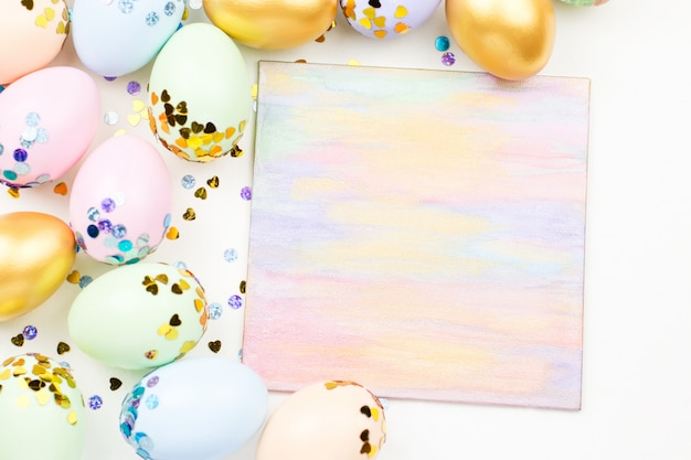 Праздничная пасха фон с украшенные яйца, цветы, конфеты и ленты в пастельных тонах на белом. копировать пространство