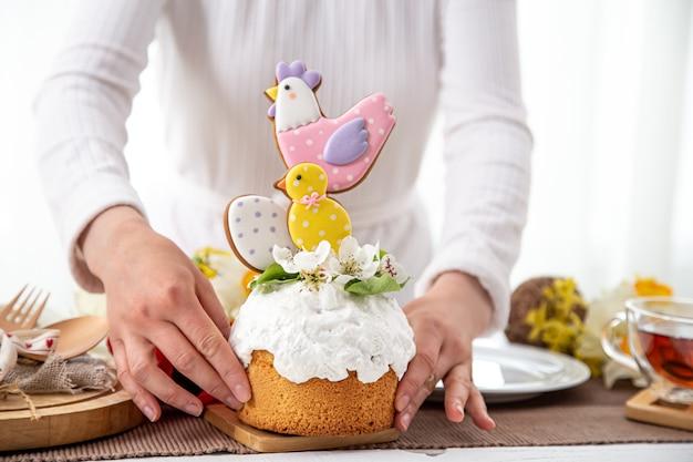 여성의 손에 축제 부활절 케이크입니다. 부활절 휴가를위한 장식의 개념.