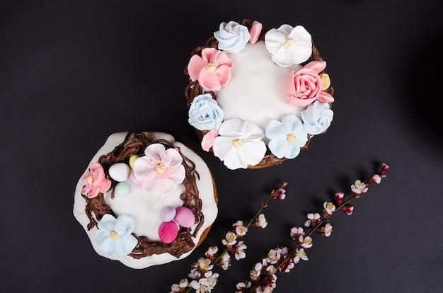 Праздничный кулич с цветочными украшениями и весенними цветами Premium Фотографии