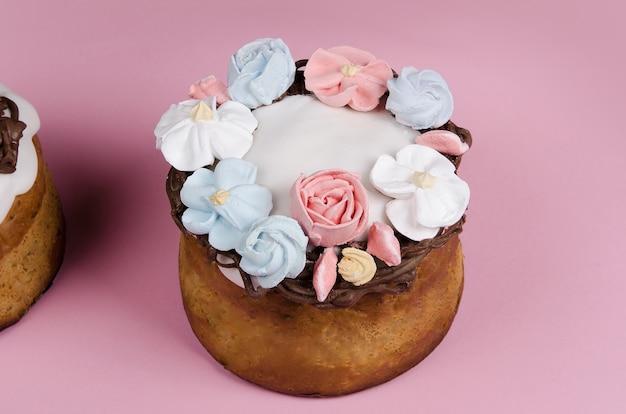 Праздничный пасхальный кулич с цветочными украшениями на розовом столе