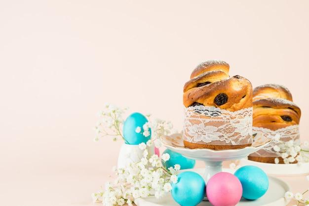 春の白い花で飾られたレーズンと着色された着色された卵のお祝いイースターケーキ。水平写真、パステル背景、コピースペース
