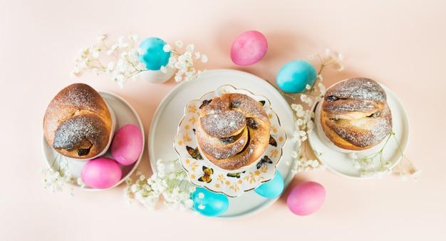 春の白い花で飾られたレーズンと着色された着色された卵のお祝いイースターケーキ。水平写真、パステル調の背景、トップビュー。