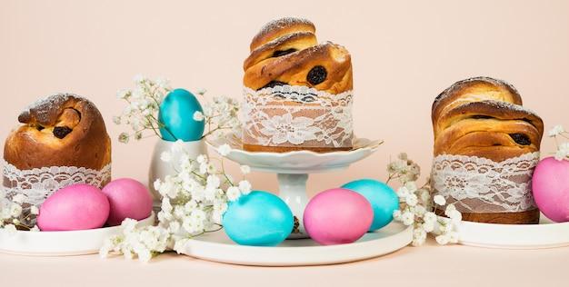春の白い花で飾られたレーズンと着色された着色された卵のお祝いイースターケーキ。水平写真、パステル背景