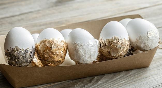 Праздничные пасхальные яйца в картонной коробке крупным планом на размытом фоне. концепция праздника пасхи.
