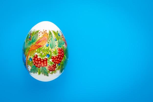 Праздничная пасхальная открытка в минималистском стиле. праздничная творческая пасхальная подарочная карта с красочным пасхальным яйцом. копировать, текстовое пространство. синий фон, рисунок.