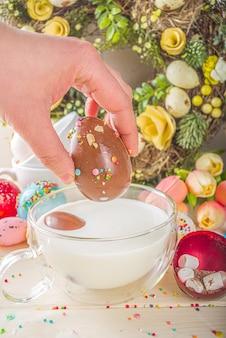 축제 부활절 핫 초콜릿 폭탄. 마시멜로와 설탕 뿌리를 곁들인 뜨거운 코코아 음료를위한 화이트 초콜릿 폭탄