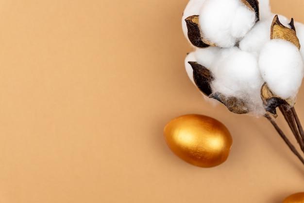 Праздничный пасхальный макет. ветвь цветка хлопка и яйца крашеные золотом на бежевом фоне. нейтральные цвета.