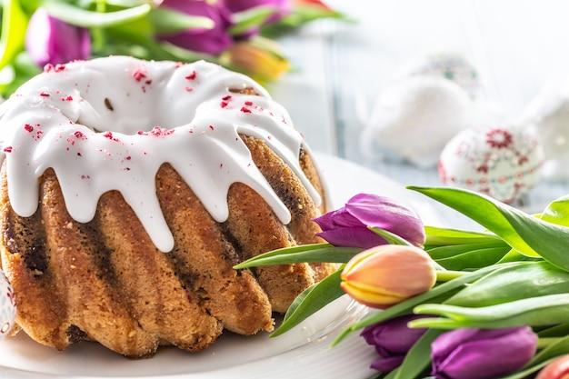 Праздничный пасхальный мраморный торт с украшенными вручную яйцами из сахарной пудры и весенними тюльпанами.