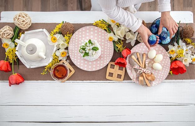 수 제 부활절 케이크, 차, 꽃 및 장식 세부 사항 복사 공간 축제 부활절 테이블. 가족 축하 개념.