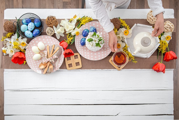 Festive easter table with homemade easter cake, tea, flowers and decor details copy space. family celebration concept.