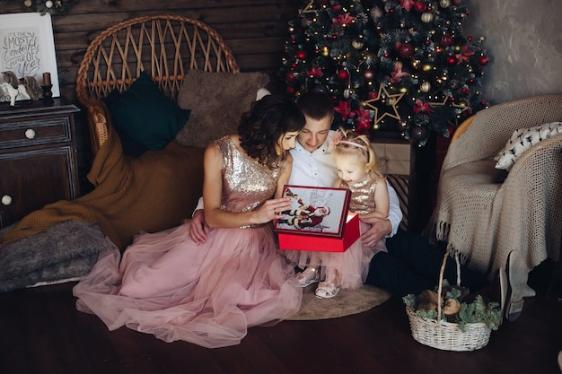 クリスマスの装飾のインテリアに囲まれたサンタクロースからのおとぎ話のギフトライトボックスを開くお祝いの家族。クリスマスの雰囲気をフルショットで楽しむ美しい母父と娘