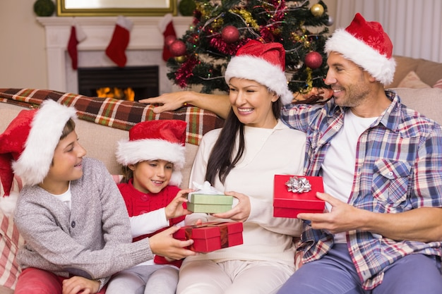 Festive family in santa hat exchanging gifts