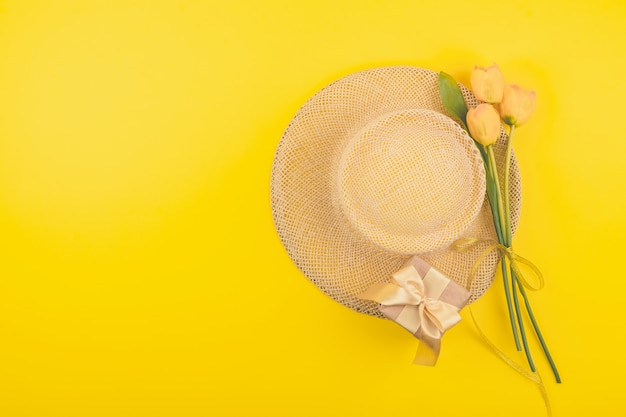 Festive female fashion flat lay with copy space. gift box, straw hat and yellow tulips