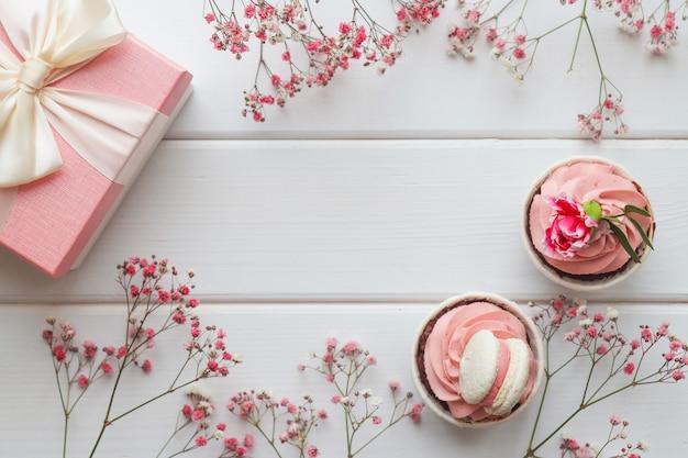 カップケーキのギフトボックスとピンクの花でお祝いのフラットレイ構成おめでとうのためのコピースペース