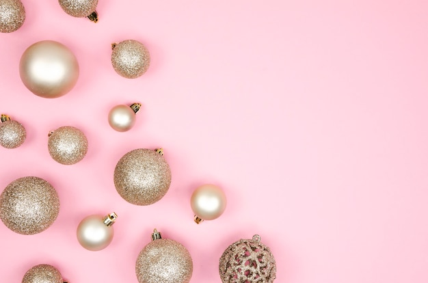 Festive flat lay frame matte golden christmas toy balls on pink background
