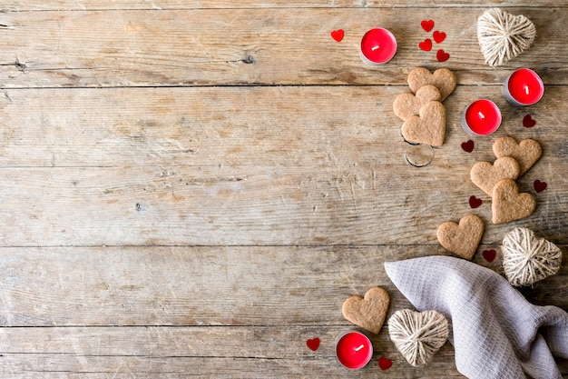 Valenrtineの日にお祝いのフラットレイは、木製の背景にクッキーの心、紙吹雪、キャンドル、ジュートヒーターを持っています