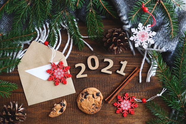 クッキー、封筒、木の数字、クリスマスのおもちゃ、クリスマスツリーの枝とお祝いのフラットレイ