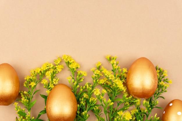 Праздничная плоская кладка с золотыми пасхальными яйцами и цветами солидаго на коричневом фоне