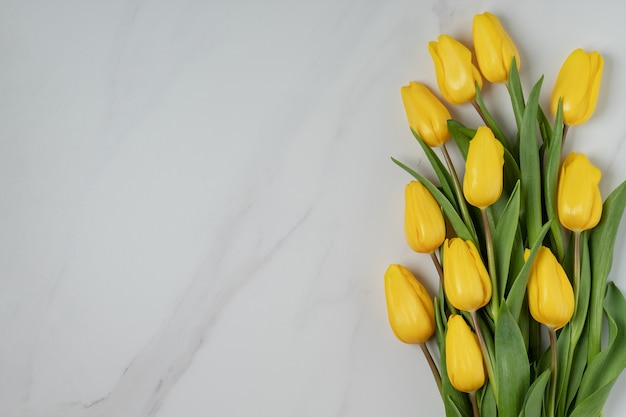 Festive flat lay with yellow tulips on marble background, copy space. spring flowers