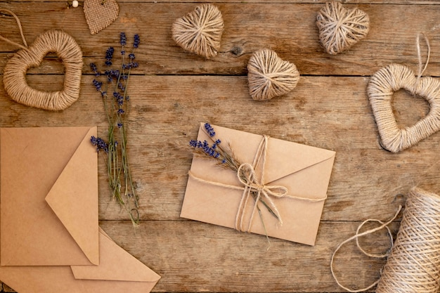 Festive flatly for valentine's day on wooden table. craft paper beige envelopes decorated with lavender flowers and jute rope. zero waste valentine's day