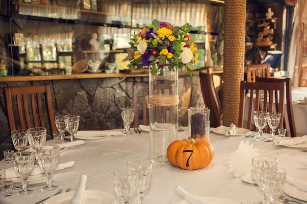 宴会場のカボチャにテーブルの番号を付けた秋のスタイルのお祝いフローリストリー。イベントのフラワーアレンジメントのフローリストリーと装飾。