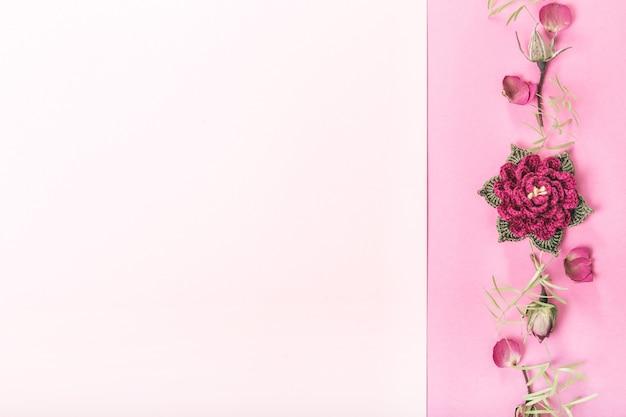 분홍색 배경에 축제 꽃 보라색 장미 구성. 오버 헤드 평면도, 평면 누워. 공간을 복사합니다. 수제 뜨개질 꽃 장미입니다. 생일, 어머니, 발렌타인, 여성, 결혼식 날 컨셉입니다.