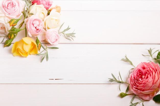 흰색 나무 바탕에 축제 꽃 노란색 영어 장미 구성. 오버 헤드 평면도, 평면 누워. 공간을 복사합니다. 생일, 어머니, 발렌타인, 여성, 결혼식 날 컨셉입니다.