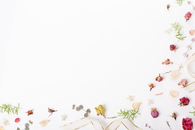 축제 꽃 구성입니다. 말린 장미 꽃, 조개, 흰색 바탕에 리본으로 만든 프레임. 오버 헤드 평면도, 평면 누워. 공간을 복사합니다. 생일, 어머니, 발렌타인, 여성, 결혼식 날 개념
