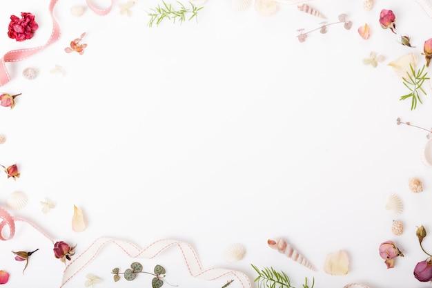 Праздничная цветочная композиция. рама из засушенных цветов розы, ракушек, ленты на белом фоне. вид сверху, плоская планировка. скопируйте пространство. день рождения, матери, валентинки, женские, концепция дня свадьбы