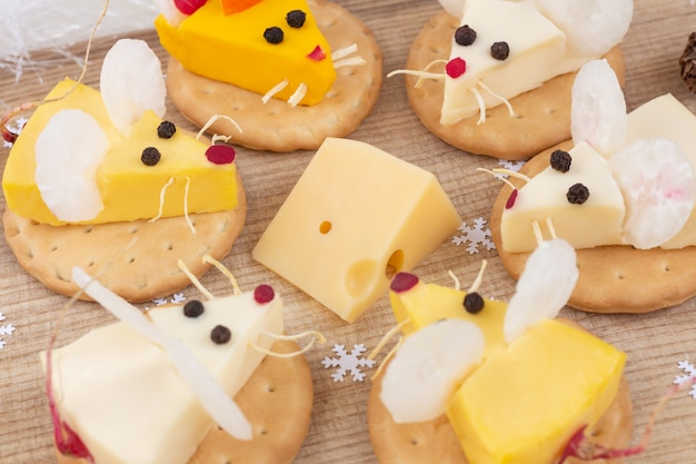 Festive food for the new year - the year of white rat. mice around a piece of cheese. appetizer. christmas mood.