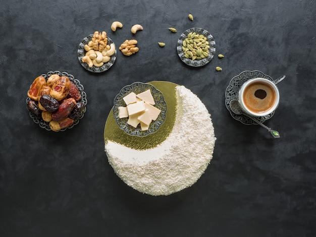 Праздничная еда рамадан. вкусный домашний торт в форме полумесяца, подается с финиками и кофейной чашкой