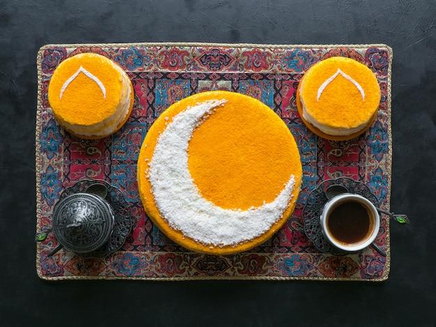 お祝い料理のラマダンの壁。三日月の美味しい自家製ゴールデンケーキ。ブラックコーヒーと日付が添えられています。上面図。