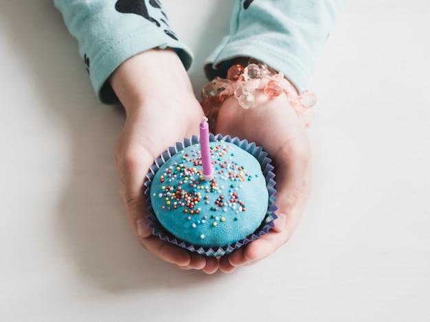 キャンドルとお祝いの香りのよいカップケーキ