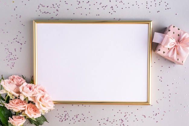 Festive frame with pink roses and a gift on a gray