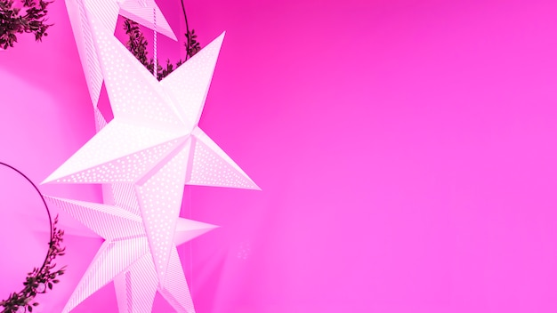 Festive garland in the form of star with light, wreaths for christmas, new year, holiday on a purple, pink background. home decor.